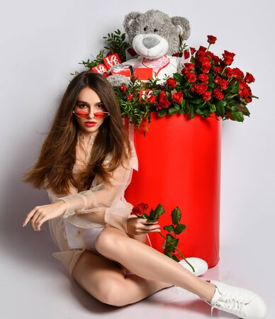 Young stylish upper-class brunette woman got a present is sitting at huge box with flowers and toy bear holding red rose on white
