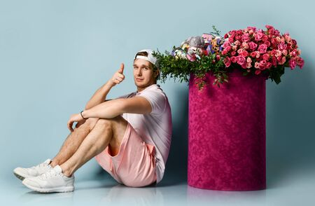 Athletic man is sitting at huge valentines day gift box with flowers roses pointing finger at us. Archivio Fotografico