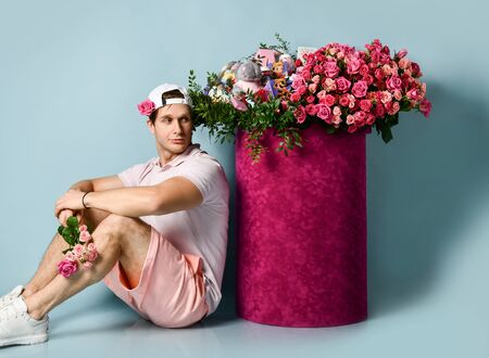 Athletic man is sitting with a bouquet of flowers at huge valentines day gift box with roses looking at it.