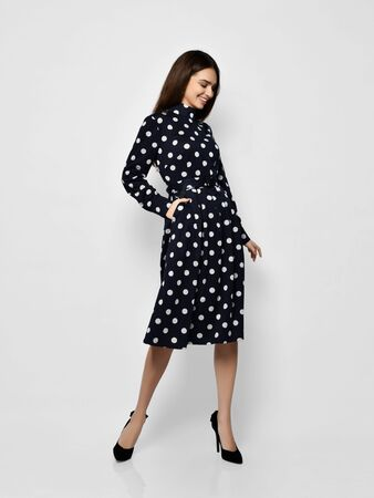 Young beautiful woman posing in new casual fashion spring blue polka dot dress full body on a white background