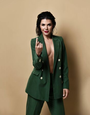 Seductive smiling young brunette woman in green costume without underwear standing in pose beckons to approach her. Stylish outfit and beauty of womans body concept