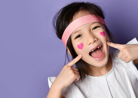 Portrait of happy smiling frolic asian Korean kid girl laughing pointing fingers on cheeks with a painted red hearts sign on her cheek with a pink headband on purple background