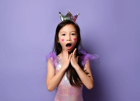 Portrait of surprised shocked asian korean kid girl princess in party dress and crown and with painted red hearts sign on cheeks on purple background