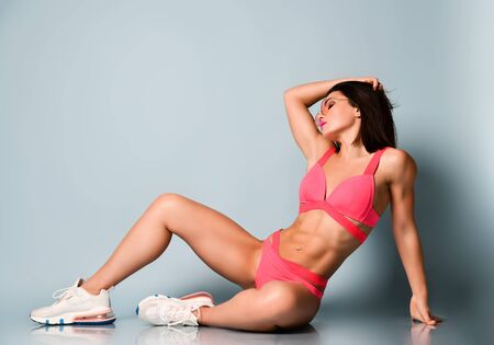 Sexy athletic woman in bright pink swimwear and sneakers sitting on the floor combing her hair adjusting hairstyle. Stylish sexy sporty outfit and beauty of womans body concept