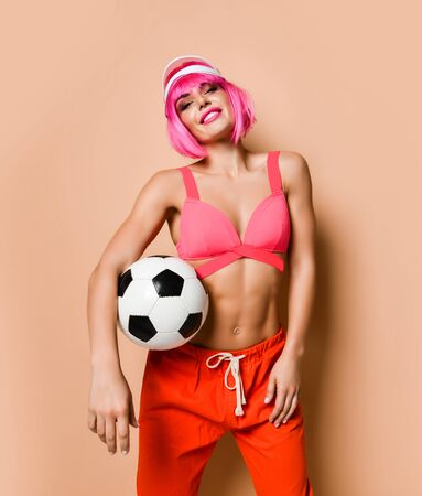 Young smiling athletic woman with pink hair in bright sportswear standing and holding soccer ball under her arm. Stylish sexy sporty outfit and beauty of womans body concept
