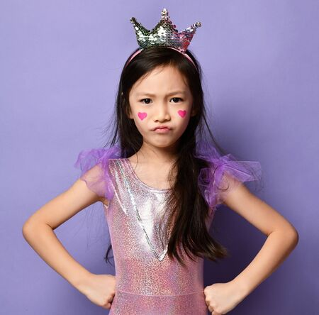 Unhappy mad asian kid girl princess in party dress, crown and with a painted red hearts sign on her cheeks is posing with her hands on her hips on purple background 版權商用圖片