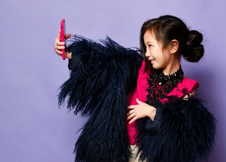 Happy smiling asian korean girl kid in luxury fashion clothes using new popular red gadget mobile cell phone making cool selfie pictures video chatting on purple background