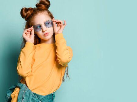 Une adolescente rousse cool en sweat-shirt jaune essaie de tenir des lunettes fumées rectangulaires bleues élégantes et regarde de côté l'espace de copie gratuit