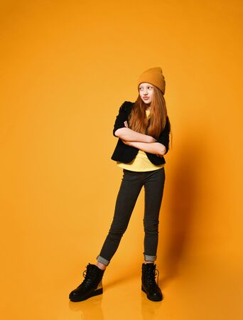 Cool red-haired teen girl in hat black jacket tight jeans and boots is standing with her arms crossed over chest watching listening reading over orange background Standard-Bild