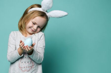 Small blond happy girl in grey cozy home clothing and white decorative fur ears standing and holding blue egg in hands over green