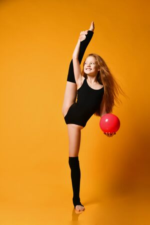 Smiling kid girl with long red hair gymnast in black swimsuit and stockings does vertical splits