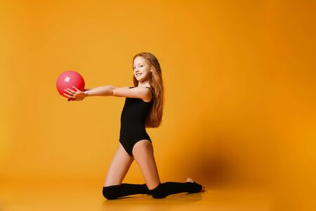 Slim kid girl gymnast in black swimsuit and stockings performs gymnastic exercise with pink ball standing on her knees holding ball at arms length in front of herself