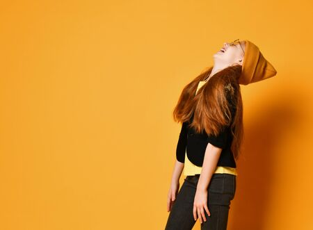 Red-haired young girl teenager in knitted hat, black jacket and tight jeans is laughing loud with her head thrown back over orange background with free text copy space