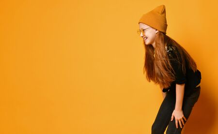 Red-haired teen girl in knitted hat, yellow glasses, black jacket and tight jeans is laughing bent over on orange background with free text copy space