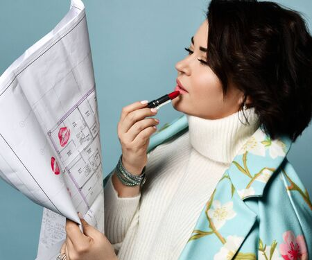 Brunette girl in white sweater and coat with floral print. She puts red lipstick on her lips and kissing blueprint or drawing of a house, posing sideways on blue background. Close up, copy space.