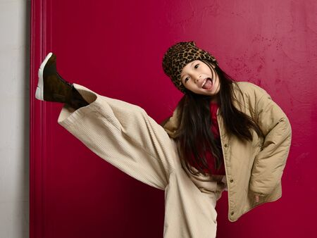 Joyful frolic asian korean kid girl in leopard print hat, fashion oversize jacket, wide velvet pants and stylish shoes is posing with her leg up, kicking over red background