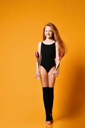 Smiling redhead teen girl gymnast in swimsuit and stockings is posing with gymnastic clubs up standing tiptoe over background with free copy space