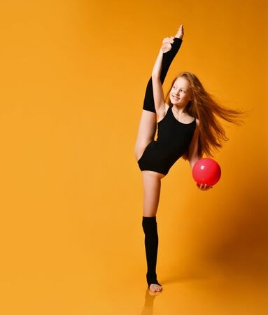 Smiling flexible redhead girl gymnast in black swimsuit and stockings does vertical splits holding a pink ball in her hand and looks aside at free copy space