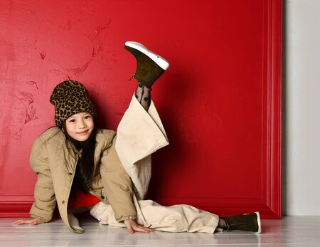 Cute smiling asian korean kid girl in fashion oversize jacket, wide velvet pants and leopard print hat is lying on the floor with her leg up over red wall background
