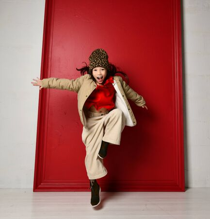 Active asian kid girl in fashion oversize jacket, red blouse, wide velvet pants and stylish shoes is jumping skipping with her arms outstretched over red wall background