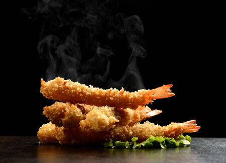 Hot and spicy langoustines prawns in batter with steam smoke on black background. Fast sea food concept