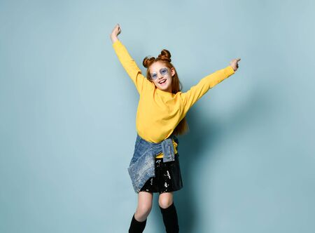 Happy smiling red-haired teen girl in yellow sweatshirt and glossy black skirt is posing with her hands up spread, dancing, ju,ping, having fun 版權商用圖片