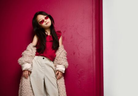 Cool asian kid girl in narrow sunglasses and wide pants is standing in slipping off her shoulders beige fur coat over red background