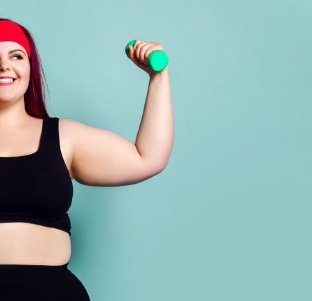 Fitness spring diet weight loss concept. Lucky plus-size girl overweight woman dieting working out with small green weights dumbbells in gym on pastel blue background