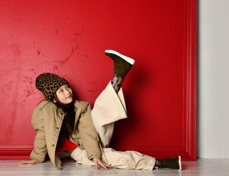 Cute smiling asian korean kid girl in fashion oversize jacket, wide velvet pants and leopard print hat is lies on the floor looking at her leg she holds up over red wall background Imagens