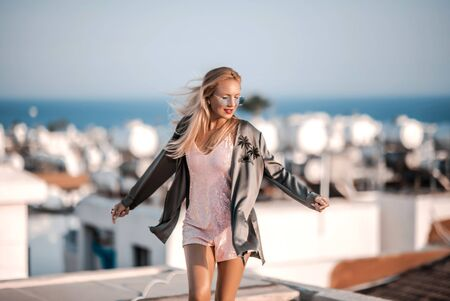 Pretty ginger hair woman traveler on vacation having fun dancing on a roof near the sea on Cyprus Imagens