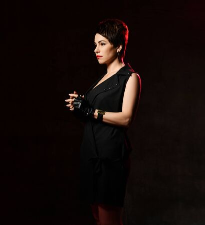 Sad, confused woman in brutal black dress with deep neckline and leather gloves with cut fingers is standing sideways holding fingers interlocked