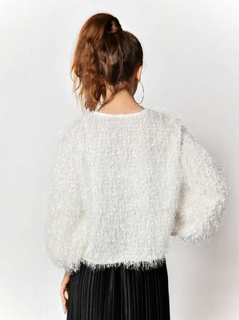 Portrait of young beautiful brunette woman with ponytail hairstyle is posing back to us in white fur sweater and pleated skirt over white background Stockfoto