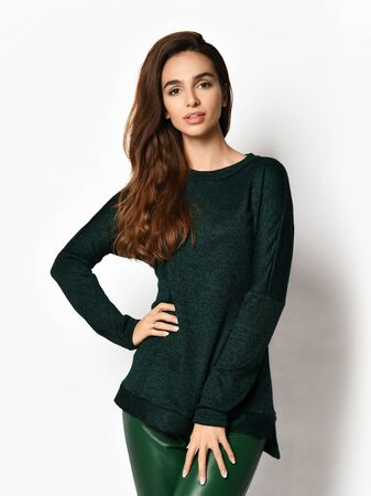 Smiling young pretty brunette woman in casual black sweatshirt jersey and brown leather jeggings is posing with her hand on her hip over white background