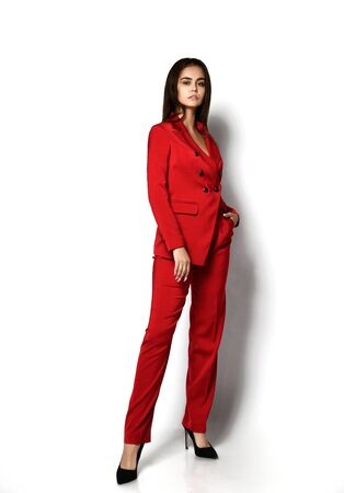 Self-confident brunette woman in stylish red office pantsuit and high-heeled shoes is posing with her foot outstretched and holding hand in her pocket