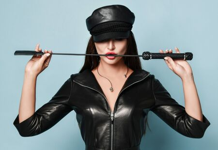 Brunette model in necklace, stylish black leather dress and cap. She is holding a whip, touching it by her red lips. Posing against blue background. Beauty, fashion, sexuality. Close up, copy space