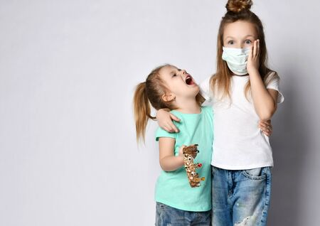 Two children are afraid of the disease in protection masks from the Coronavirus Covid-19 hold gold crown corona symbol of madness pandemic panic epidemic spreads across the globe