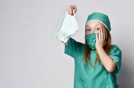 Little girl child play doctor in green medical coat hold protection masks from the Coronavirus Covid-19 surprised. Madness pandemic panic epidemic spreads across the globe
