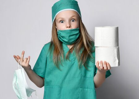 Little girl in a medical coat holds bactericidal protection mask from the Corona Virus and toilet paper rolls surprised. Madness pandemic Coronavirus Covid-19 panic epidemic spreads across the globe