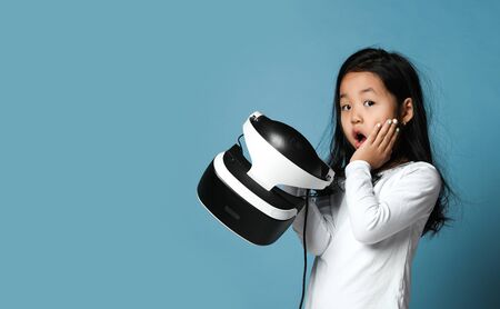 Young girl kid child play virtual reality game hold vr glasses and surprised. Cyber space and virtual gaming. Discover future technology on blue background with text space