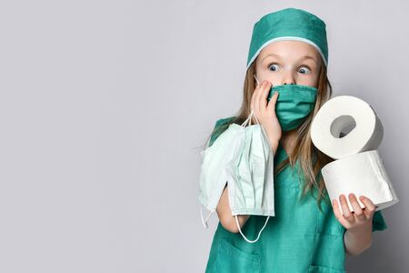 Little girl kid in medical coat holds  protection masks from the Corona Virus and toilet paper rolls Preparing for a Pandemic surprised. Coronavirus Covid-19 panic epidemic spreads across the globe 写真素材