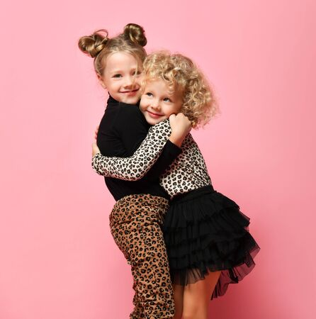 Laughing kids girls friends sisters in leopard print clothes pants and sweater are running jumping hugging hold hands together pointing fingers on pink background Stock Photo