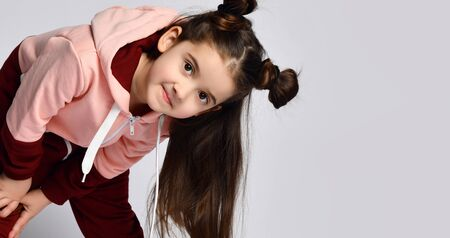 Frolic curious kid girl with straight brunette hair with buns in modern fashion pink brown sportwear is bending over to peek in camera on gray background with free text copy space