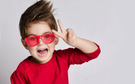 Little brunet child with stylish hairstyle, in sunglasses, red jumper. He opened mouth, showing victory sign, posing isolated on white background. Childhood, fashion, advertising. Close up, copy space