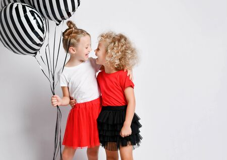 Happy kids girls sisters in red and black skirts celebrate birthday are screaming singing songs playing celebrating having fun at party with stylish air balloons on white Stock Photo