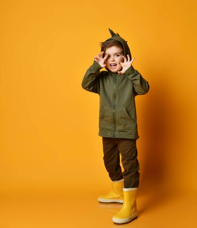Kid boy in green hoodie with dinosaurus spikes at cowl and rubber boots wellies plays t-rex beast looking at us with his hands claws up over background with free copy space