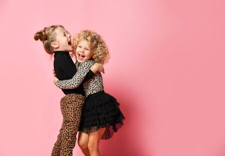 Two happy kids blonde girls best friends sisters in leopard print clothes pants and sweater are hugging laughing over pink background with free copy space 写真素材 - 143209615