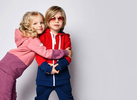 Portrait of two kids in stylish sportswear. Curly hair blonde kid girl is hugging her friend brother blond kid boy over white background with free copy space