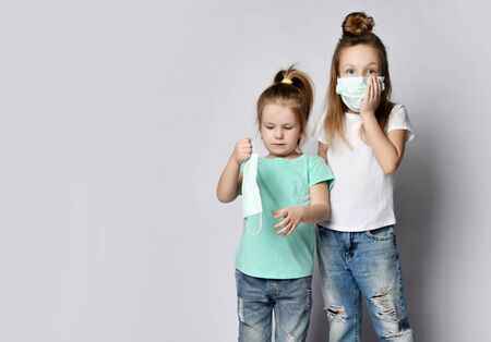 Two children girls kids are afraid of the disease in protection masks from the Coronavirus Covid-19 Madness pandemic virus panic epidemic spreads across the globe