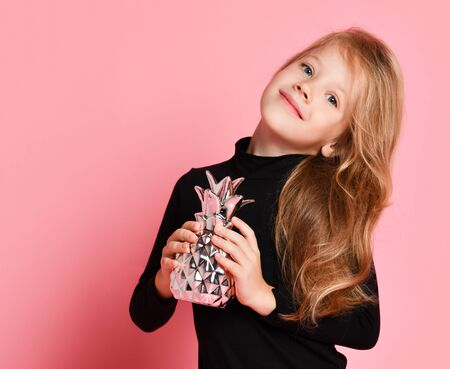 Nice smiling blonde kid girl in black sweatshirt poses with silver pineapple she holds in her hands over pink background