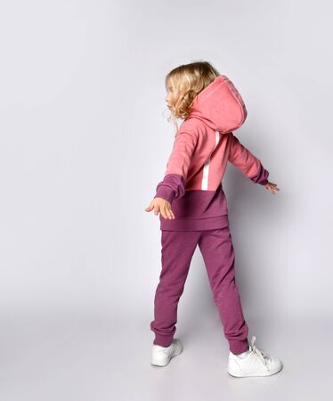 Curly hair blonde kid girl in modern fashion pink gray sportsuit stands back to us with her arms outstretched wide spread  spinning turning over white background